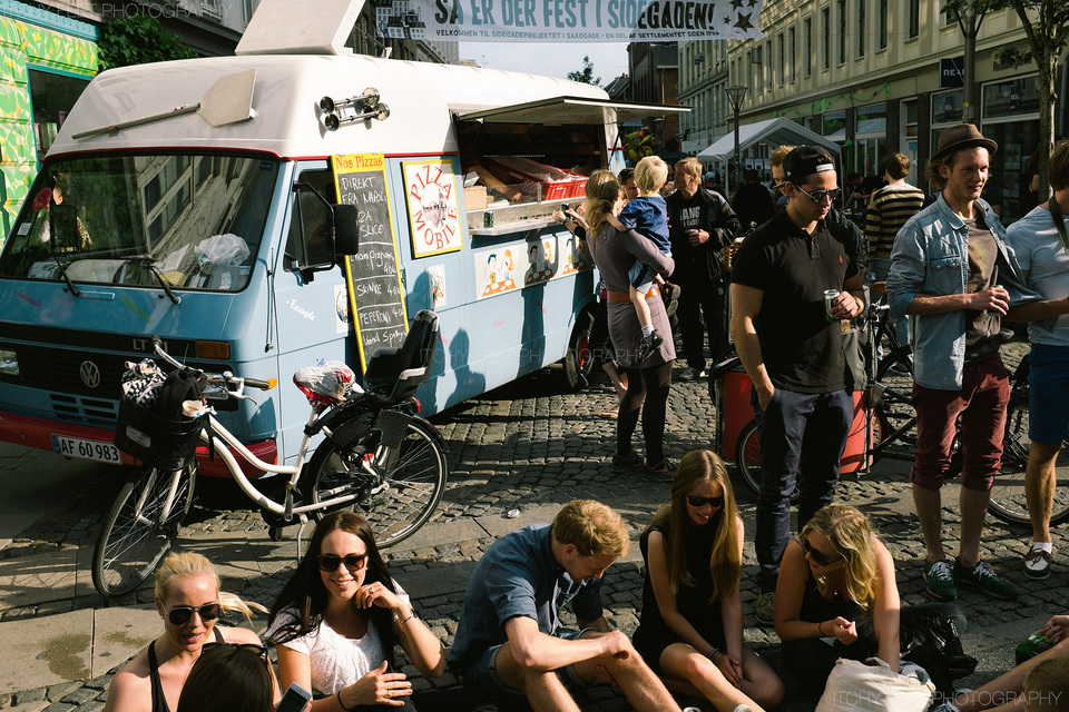 People enjoying the sun and some pizza from the funky pizza van